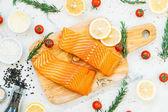 Syrové a čerstvé maso losos filet na dřevěném prkénku s citronem rajčaty a další složkou - zdravé potraviny styl