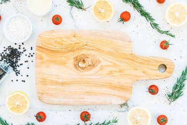 Empty wooden cutting board with copy space and lemon tomato and other ingredients