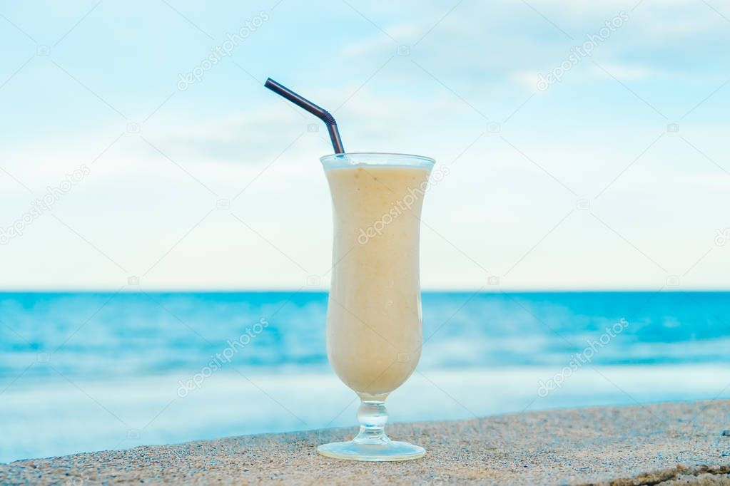 Ice drinking banana smoothies glass with sea and ocean background
