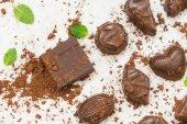 Sladký moučník s kousky tmavé čokolády a kakaový prášek na bílém pozadí kamene