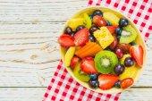 Smíšené a různé ovoce s jahoda kiwi hroznů a dalších v misce na dřevěný stůl - filtr zpracování