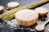 Photo Raw Jasmine rice in wooden bowl  and spoon with grain and seed