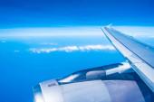 Luftaufnahme des Flugzeugflügels mit blauem Himmel
