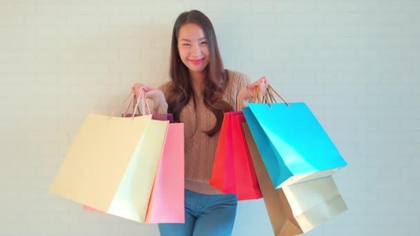 záběry krásné asijské ženy s nákupními taškami před bílou stěnou