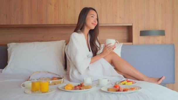záběry krásné asijské ženy pití kávy při snídaní v posteli doma