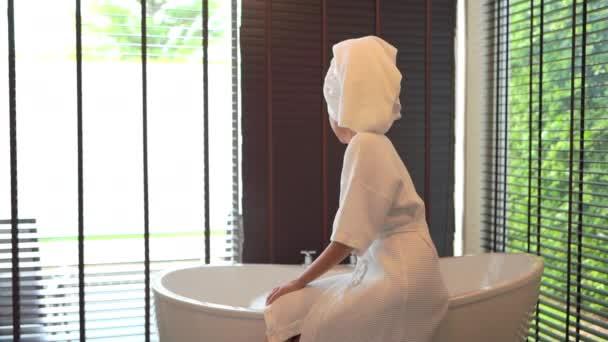 záběry krásné asijské ženy ve vaně s mýdlovými bublinami