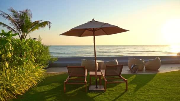 Krásná tropická pláž moře oceán s deštníkem a židle kolem kokosové palmy na modré obloze pro volný čas dovolená