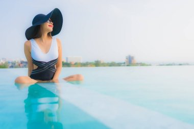 Portrait beautiful young asian woman happy smile relax around outdoor swimming pool in hotel resort for travel vacation