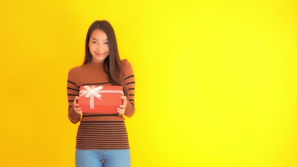felvétel gyönyörű ázsiai nő kezében piros ajándék doboz elszigetelt sárga