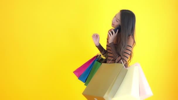 záběry krásné asijské ženy drží barevné papírové nákupní tašky izolované na žluté