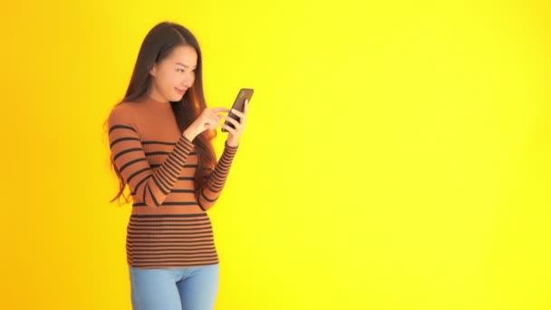 Filmmaterial von schönen asiatischen Frau mit Smartphone isoliert auf gelb