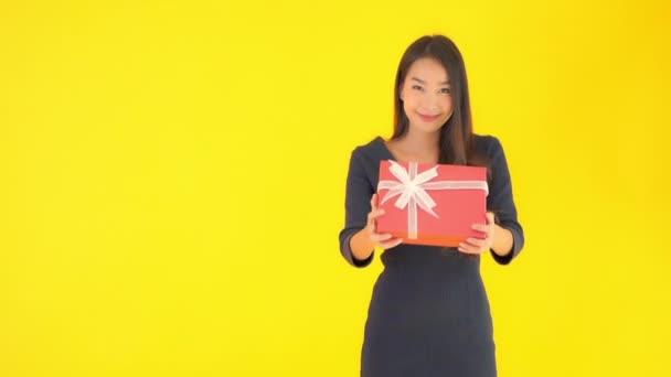 záběry krásné asijské ženy držící červenou dárkovou krabici izolované na žluté