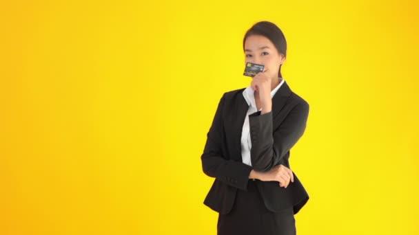 felvétel gyönyörű ázsiai üzletasszony fekete öltöny gazdaság hitelkártya elszigetelt sárga