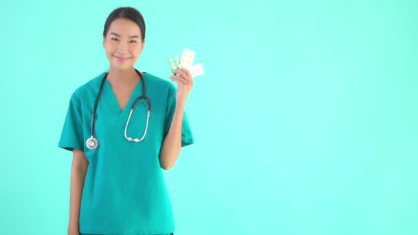 Portrét krásné mladé asijské lékař žena s pilulky nebo léky a léky na modrém izolovaném pozadí