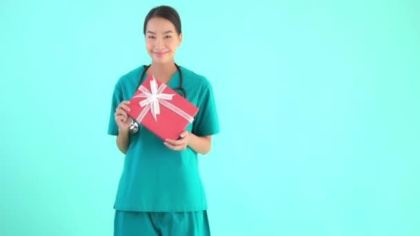 Portré gyönyörű fiatal ázsiai orvos nő gazdaság rózsaszín ajándék doboz kék elszigetelt háttér
