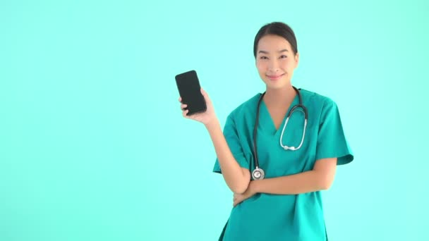 Portrait beautiful young asian doctor woman holding phone with blank screen on blue isolated background