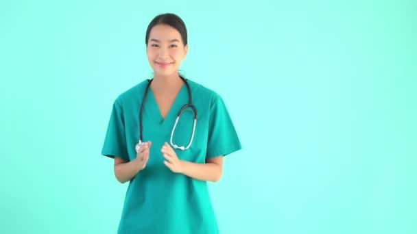 Porträt schöne junge asiatische Ärztin macht namaste Geste auf blauem Hintergrund isoliert