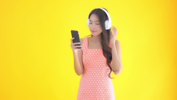 footage of beautiful Asian woman using smartphone and listening music with headphones isolated on yellow