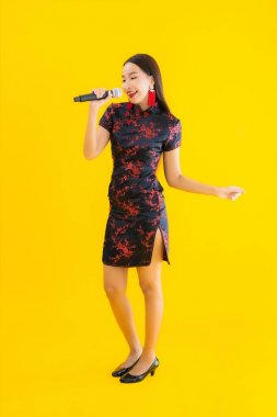 Portrait beautiful young asian woman wear chinese dress show singing music on yellow isolated background