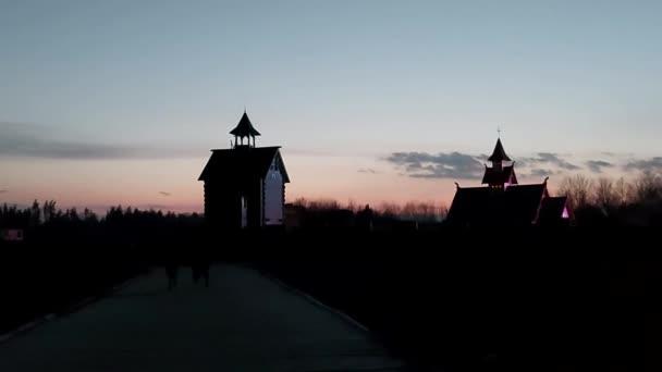 Neidentifikovaní lidé jdou ke kameře, na pozadí dřevěné budovy, západ slunce