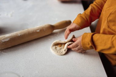 grandson sculpting pies on the kitchen table with rolling pin