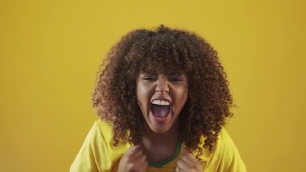 Mladý brazilský kudrnatý žena gestikulace a pózování na žlutém pozadí