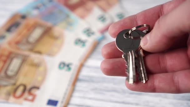 Nové lesklé klíče od domu na pozadí hromady eurobankovek na bílém dřevěném stole. Pochybnosti při výběru domu nebo bytu na nákup a pronájem