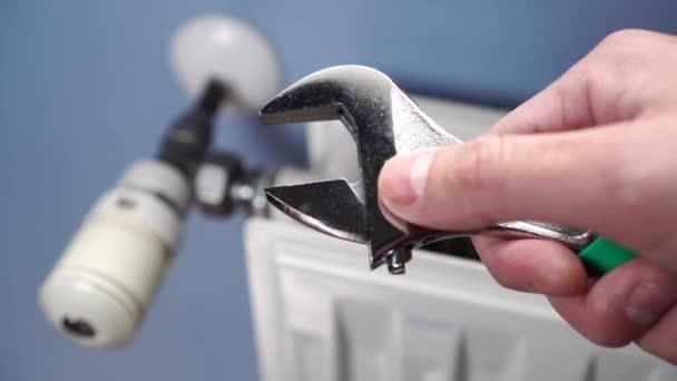 Eine männliche Hand justiert einen verstellbaren Schraubenschlüssel gegen einen Heizkörper an einer blauen Wand. Reparatur und Wartung von technischen Systemen zu Hause