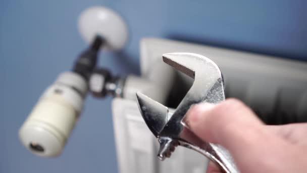 Mužská ruka nastaví nastavitelný klíč proti topnému radiátoru s termostatem na modré stěně. Opravy a ladění strojírenských systémů doma