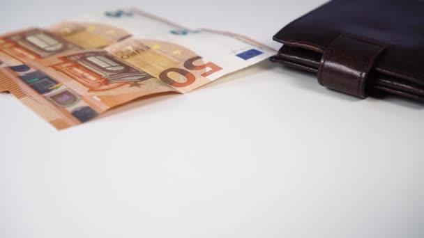 Lesklé nové klíče od bytu s eurobankovkami a peněženkou na bílém pozadí. Nákup nebo pronájem bytu v agentuře