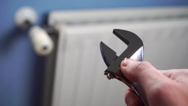 Einstellschlüssel in der Hand eines männlichen Reparateurs auf dem Hintergrund eines weißen Heizkörpers an einer blauen Wand. Reparatur und Installation einer Heizungsanlage in einem Wohnhaus