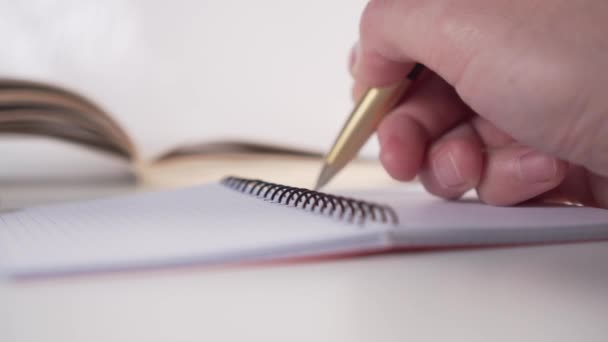 A young man writes with a golden pen in a planner with black spiral pages on a desk with a book in the background. The concept of self-discipline in business