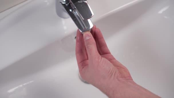 Montage und Inspektion des Filters mit Gummidichtung des glänzenden öffentlichen Toilettenhahns nach der Reinigung. weiße saubere Spüle. Instandhaltung der Sanitäranlagen. Schlosserhand wickelt das Teil und dreht dann auf dem Wasser auf