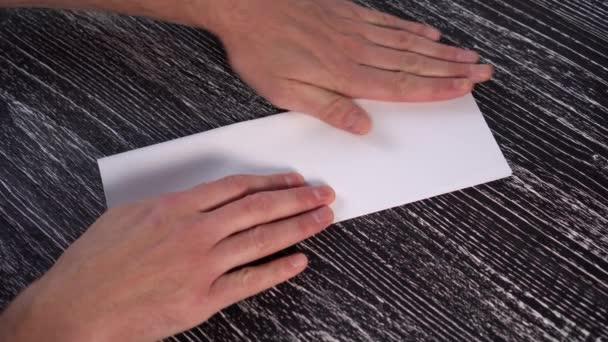 ein junger Mann bastelt ein Origami-Flugzeug aus einem weißen Blatt Büropapier auf einem schwarzen strukturierten Holztisch.