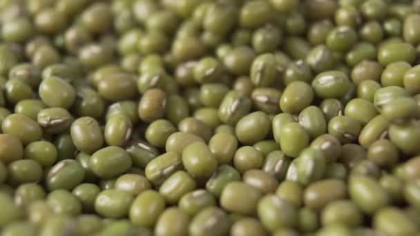 Grüne Mungbohnen fallen in einen Haufen. Zeitlupe. Makro