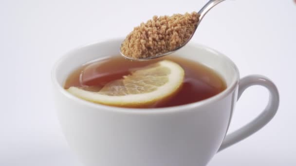 White cup with black hot tea with a slice of lemon. A dessert spoon lays cane sugar and mixes the drink. Vitamin Tonic