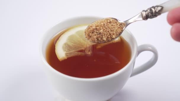kézzel hozzá nádcukor egy desszert kanál egy csésze forró fekete tea és egy szelet citrom közelkép. forró vitamin ital az immunitás javítása érdekében