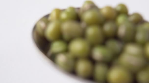 Löffel gießt einen Bund Mungbohnen auf einen weißen Tisch. Zeitlupe. Makro