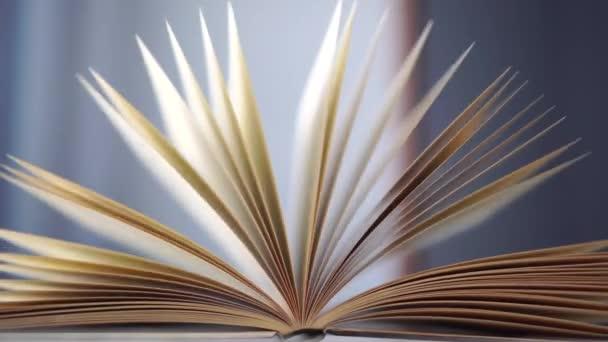 Szekrény nyitott régi keménykötésű könyv régi fa könyvtár asztal kék fal. Az oldalak lassan ingadoznak..