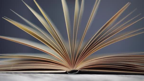 Otevřít starou knihu zblízka. Žluté stránky se pohybují ve větru. Na starém dřevěném stole v knihovně. Modré pozadí.