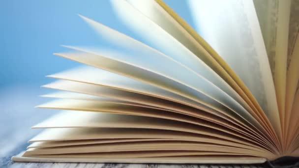 Régi keménykötésű könyv sárga oldalai az antik fa asztalról. Megingott a széltől a napsütéses reggeli sugarakban. Kék, fényes háttérrel. Az otthoni távoktatás fogalma