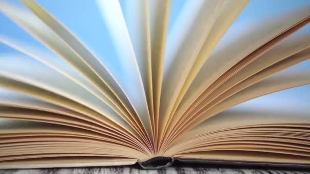 Na starožitném dřevěném stole se pohupují stránky staré knihy z tvrdého obalu. Ve slunečných ranních paprscích. Na modrém, jasném pozadí. Koncept samovýchovy během karantény