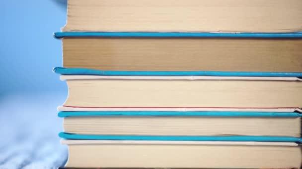 hromada starých knih se hromadí na starém dřevěném stole. Na jasně modrém pozadí. Detailní záběr. Kamera se pohybuje nahoru
