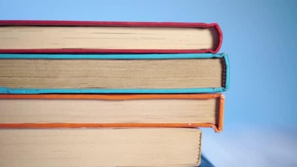 hromada starých knih v pevném a měkkém obalu na modrém jasném pozadí. Na starém dřevěném stole. Detailní záběr. Kamera se pohybuje dolů
