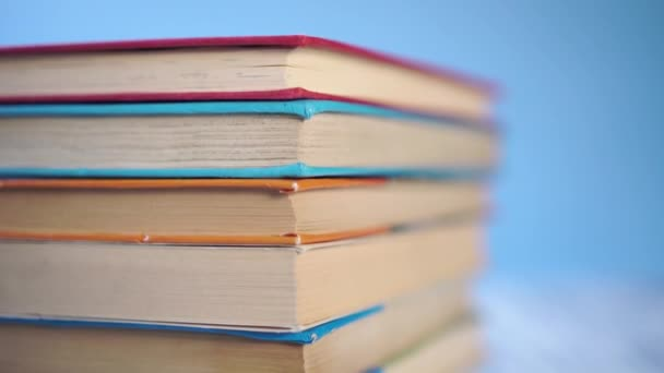 stack of colorful hardback books on a blue bright background. On a wooden old table. Close-up. The camera moves down