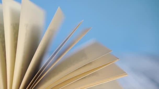 Na starožitném dřevěném stole se pohupují stránky staré knihy z tvrdého obalu. Na modrém, jasném pozadí. Koncept samovýchovy během karantény