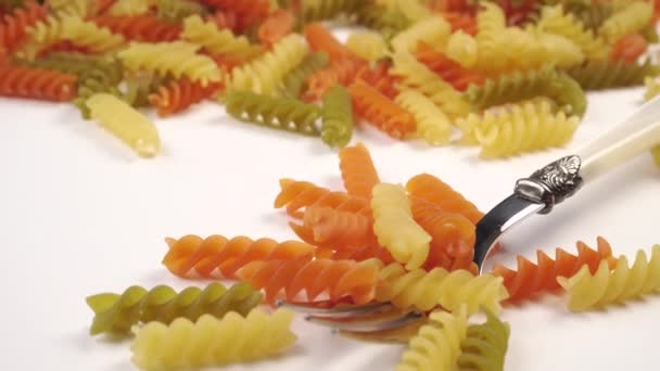 pile of vegetable colored pasta on a fork on a white table close-up. macaroni raw. The camera moves down