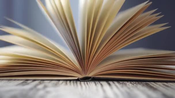 Nyitott könyv közelkép egy kék háttér a könyvtárban. Egy régi fa fekete-fehér asztalon. A lapok lassan ringanak.