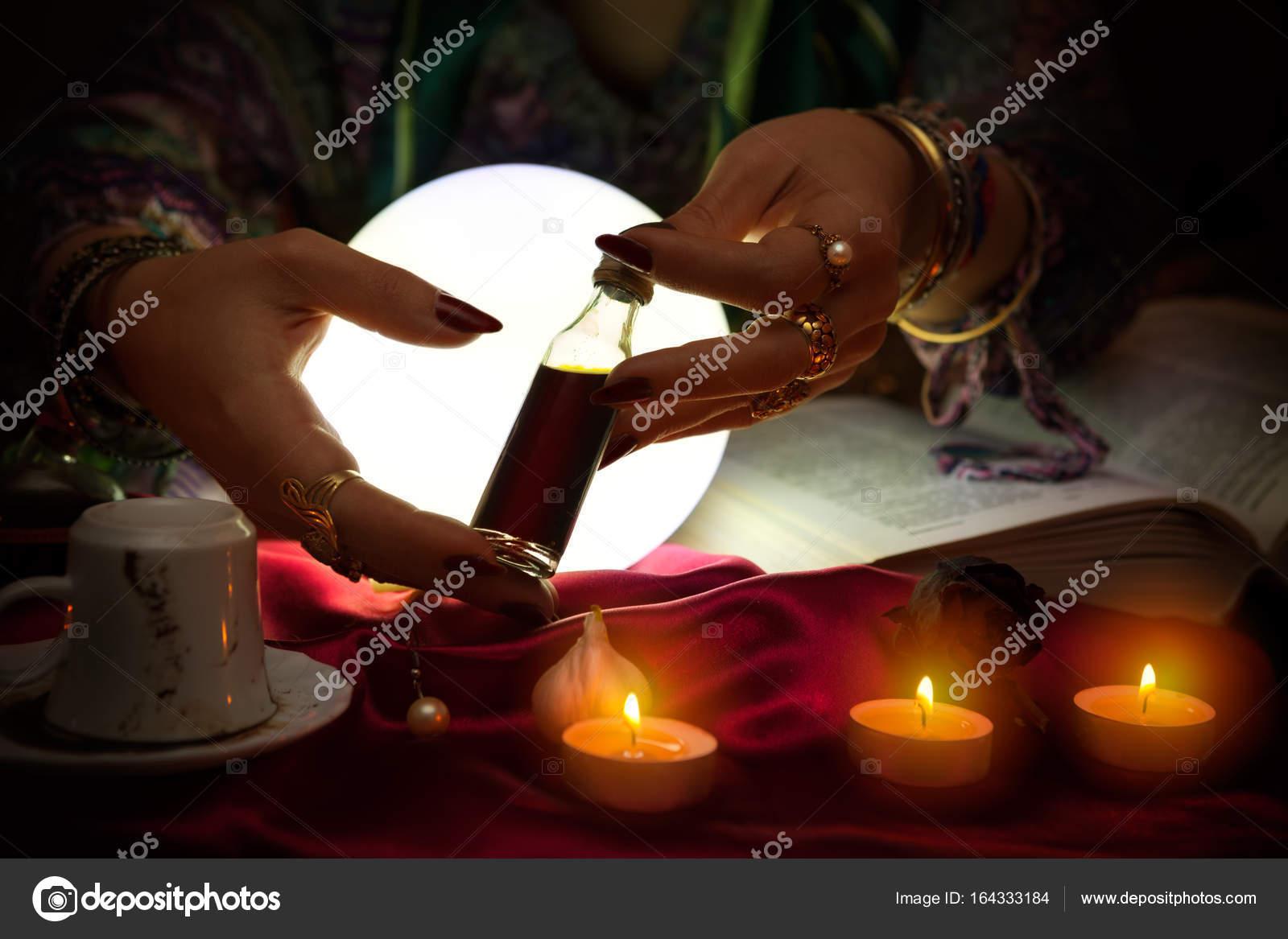 Bottle of love potion in hands of fortune teller — Stock