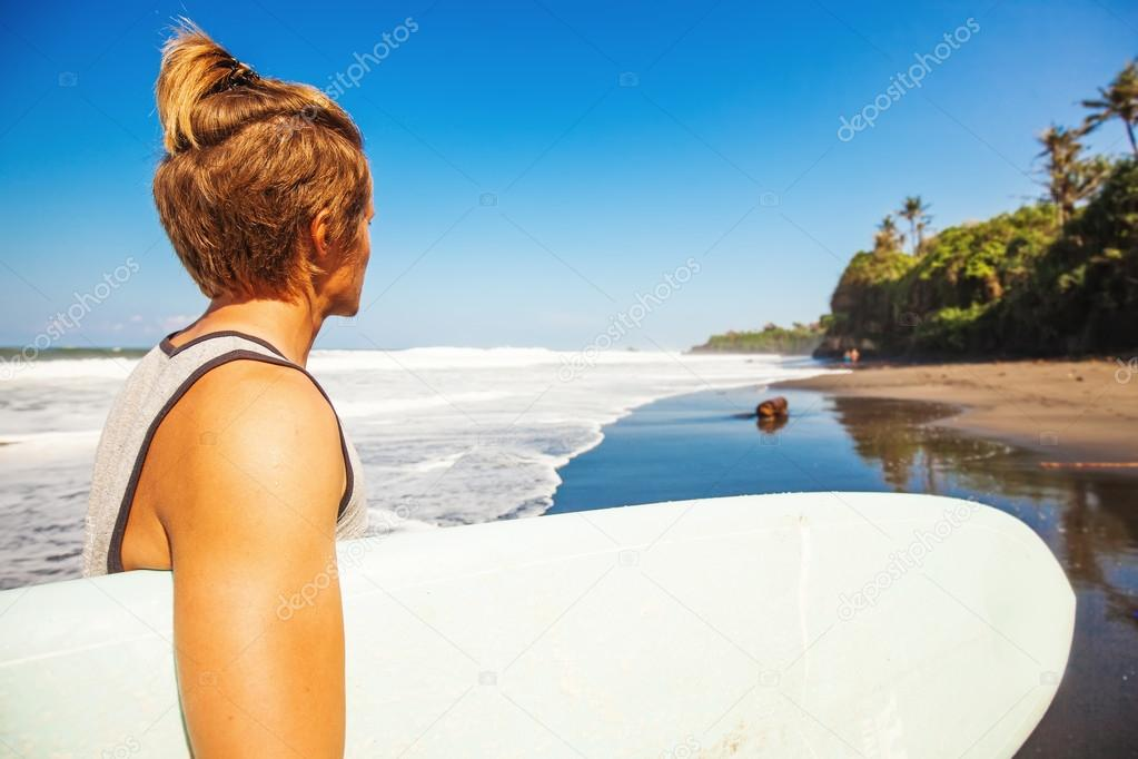 man on beach with surf board
